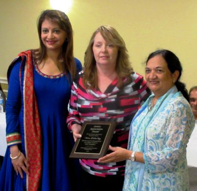 Clinic chief nurse Debbie Ray gets an award from Anjali Patel (left) and Bharati Desai