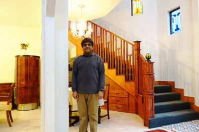 Atul Vir in front of the new curved wooden staircase, wooden bannisters and a cantilevered second floor space.