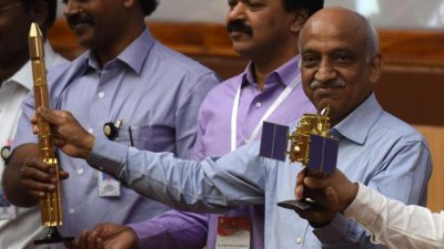 ISRO chairman Kiran Kumar Rao (R) displays models of the CARTOSAT-2 and Polar Satellite Launch Vehicle (PSLV-C37) as he speaks to media after the launch of the Polar Satellite Launch Vehicle (PSLV-C37) at Sriharikota on Febuary 15.(AFP Photo)