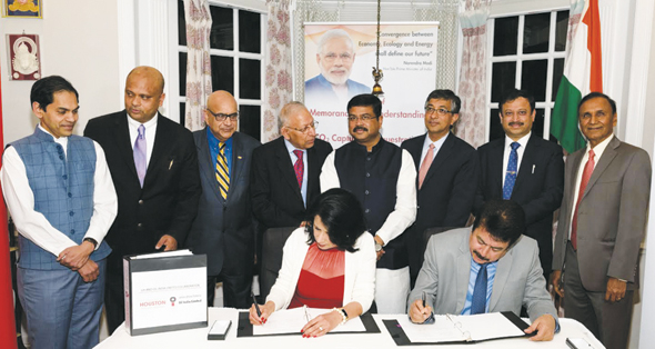 Indian government officials, including Minister Pradhan (center), UH scientists, and community leaders watch UH Chancellor Renu Khator and OIL CMD Utpal Bora sign the MOU. Photo: Bijay Dixit
