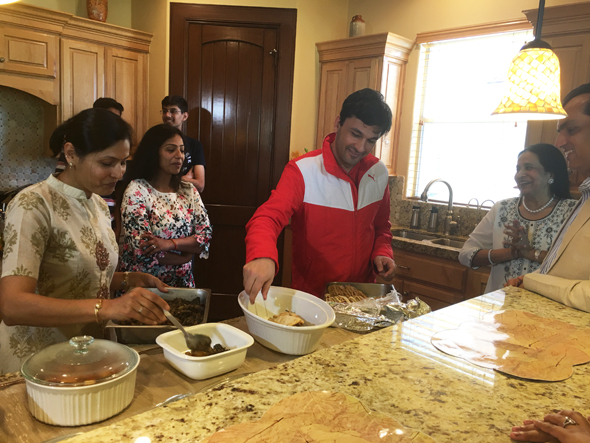 Chef Vikas Khanna helping Shalu Agarwal set up naans for lunch.