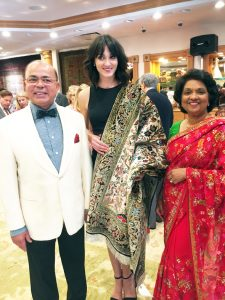 Abrahams Oriental Rugs and Treasures owners Sam and Omana Abraham pose on the floor of their new Post Oak store with one of several fashion models, who were presenting a selection of the luxurious oriental rugs that were available for sale at a special discount.