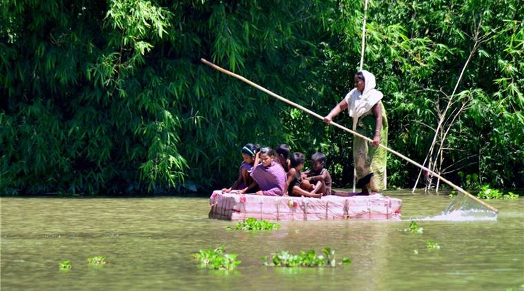 Kamrup: A woman with her children rows a makeshift raft across flood waters in the Kamrup district of Assam on Friday. (PTI file Photo)