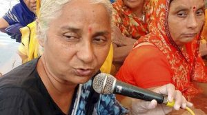"""Badwani: Social activists Medha Patkar and other villagers stand in water of Narmada river to protest the birthday celebration of Prime Minister Narendra Modi by inaugurating the construction of Sardar Sarovar Dam, during """"Jalsatyagrah"""" at Chhota Barda Village in Badwani district of Madhya Pradesh on Saturday. (PTI Photo)"""
