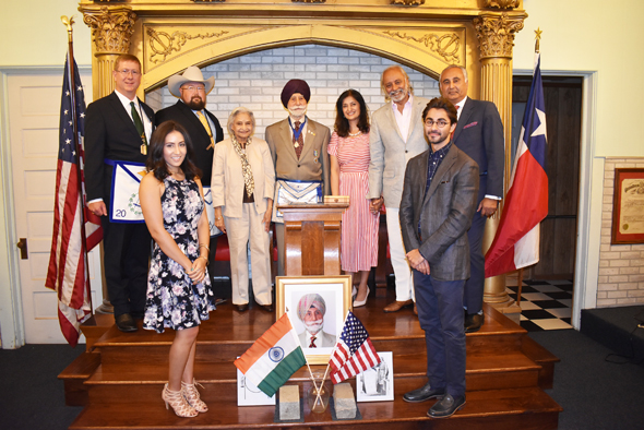Raj Bhalla with his family and fellow Masons. In backrow, from left are District Deputy Grand Master Albert Davis, Worshipful Master Cody Cockroft, wife Kanwal Bhalla, daughter-in-law Dr. Jyotish Bhalla, son Gurpreet Bhalla, and son Narinder Bhalla. In front on either side of his portrait are, from left, granddaughter Sonya Bhalla and grandson Ravi Bhalla.