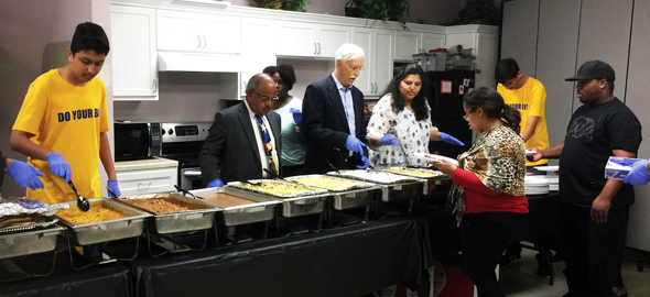 "Rahul and Varun Agarwal (in yellow ""Do Your Bit"" shirts) serve a Thanksgiving meal to the disabled at the Volunteers of America center along with representatives of Indo-American and other charitable organizations."