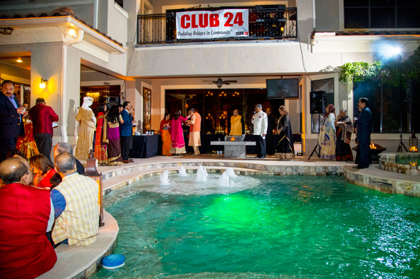 Club 24 Plus leaders made their brief remarks under the banner of the charitable organization with members gathered around the colorfully lit pool.
