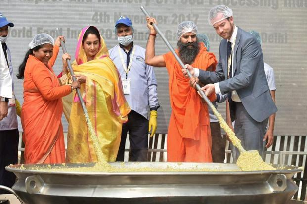 Union minister of food processing Harsimrat Kaur Badal along with Sadhvi Niranjan Jyoti, MoS for food processing, and Swami Ramdev cooking 'khichdi' in a giant wok at the World Food India 2017 festival in New Delhi on Saturday to create a world record. Photo: PTI