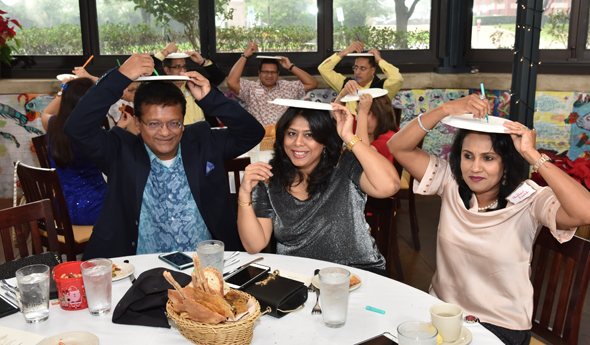 Ash and Leena Shah (left) and Madhavi Kavadi attempt to draw a Holiday scene on a paper plate held on top of their heads.