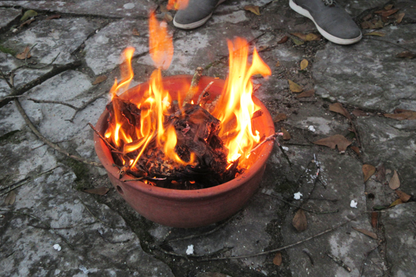 A micro-bonfire of twigs collected from the garden burns in a clay pot
