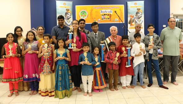 Organizers and winners. Back row (from right): iBAM Founding-Donor Anand Mohan Bhagavatula;iBAM Secretary Arunakanth Duvvury;iBAM President Mallik Putcha; Chief Guest Vice Consul-General of India Sabyasachi De; TCA President Brahmananda Reddy Beriveera; TCA Cultural Secretary Srinivas Manthena and TCA Literary Co-ordinator Indira Cheruvu. Trophy Winners (from left): Lakshmi Kandala(iBAM Potana); Naagita Sanvi Kumpatla(iBAM Potana); Advitha Udthawar(iBAM Potana); Srividya Kandala(iBAM Potana); Ananya Basavaraju(iBAM Potana); Gayatri Pemmaraju(iBAM Potana & iBAM Gajendra); Abhiram Dhulipala(iBAM Potana); Vaishnavi Renduchintala (iBAM Potana& iBAM Gajendra); NIkhil Maddineni(iBAM Potana); Akhil Velagaleti(iBAM Potana & iBAM Gajendra); Kaushal Pemmaraju(iBAM Potana) and Vikas Thoutam(iBAM Potana).