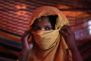 AP Photo/Wong Maye-E, File). FILE- In this Thursday, Nov. 23, 2017, file photo, S, 22, mother of one, who says she was raped by members of Myanmar's armed forces in late August, is photographed in her tent in Gundum refugee camp in Bangladesh.