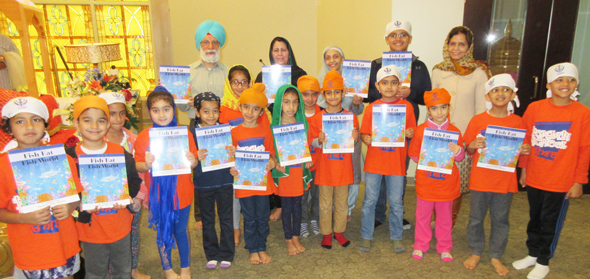 The kids from the school surrounded Singh, Likhari and teacher Manjit Soni with copies of the book they received.