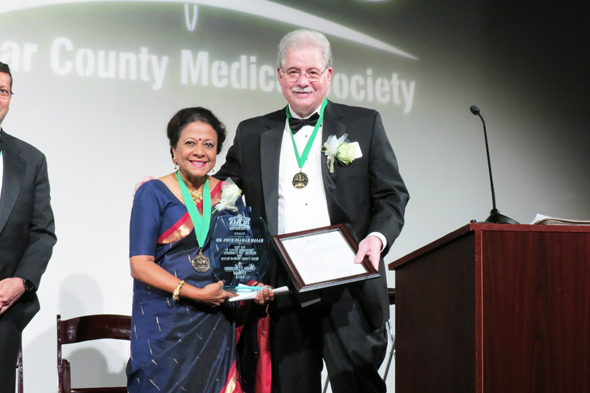 Dr. Rajam Ramamurthy, receiving the Golden Aesculapius Award from Dr. Sheldon Gross, President of the Bexar County Medical Society. It is the highest honor given to a physician for services to medicine and the society.