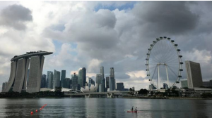 FILE – In this Wednesday, April 20, 2016, file photo, two kayaks are dwarfed against the skyline of the Marina Bay area, which is home to popular hotels, and tourist attractions such as the Singapore Flyer, the city-state's observation wheel seen at right, in Singapore. (AP Photo/Wong Maye-E, File)