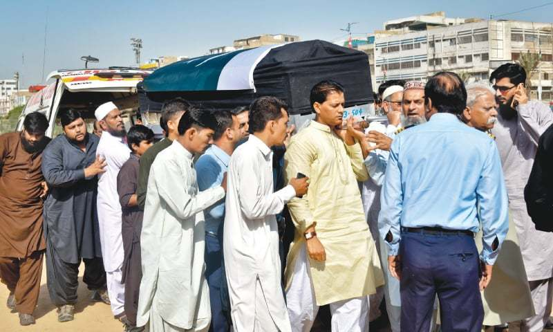 RELATIVES carry the coffin of Sabika Sheikh, wrapped in the national flag, for funeral prayers on Wednesday.-Fahim Siddiqi / White Star
