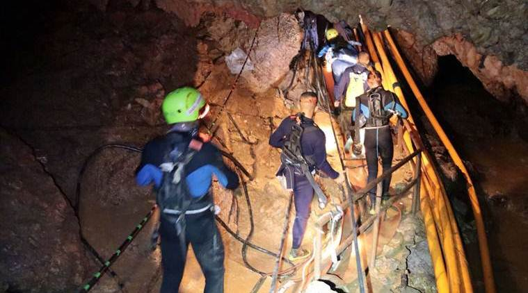 Thai cave rescue LIVE: In this undated photo released by Royal Thai Navy, Thai rescue team members walk inside a cave where 12 boys and their soccer coach have been trapped since June 23, in Mae Sai, Chiang Rai province, northern Thailand. (AP)